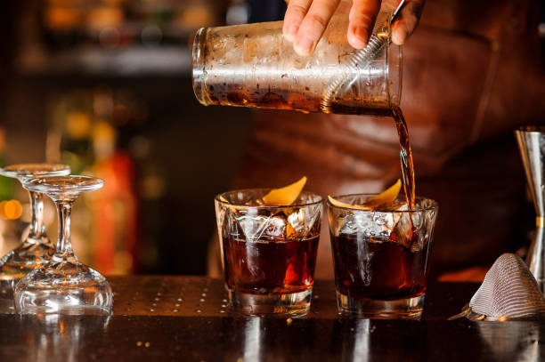 Bartender pouring alcoholic drink into the glasses Bartender pouring fresh alcoholic drink into the glasses with ice cubes on the bar counter bartender stock pictures, royalty-free photos & images