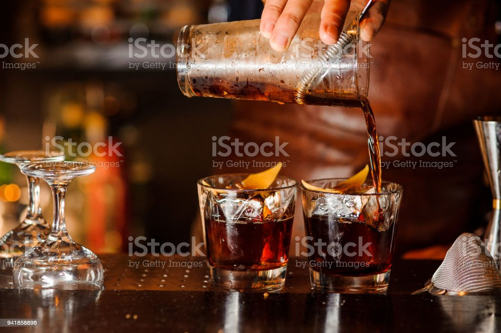 Bartender pouring alcoholic drink into the glasses stock photo
