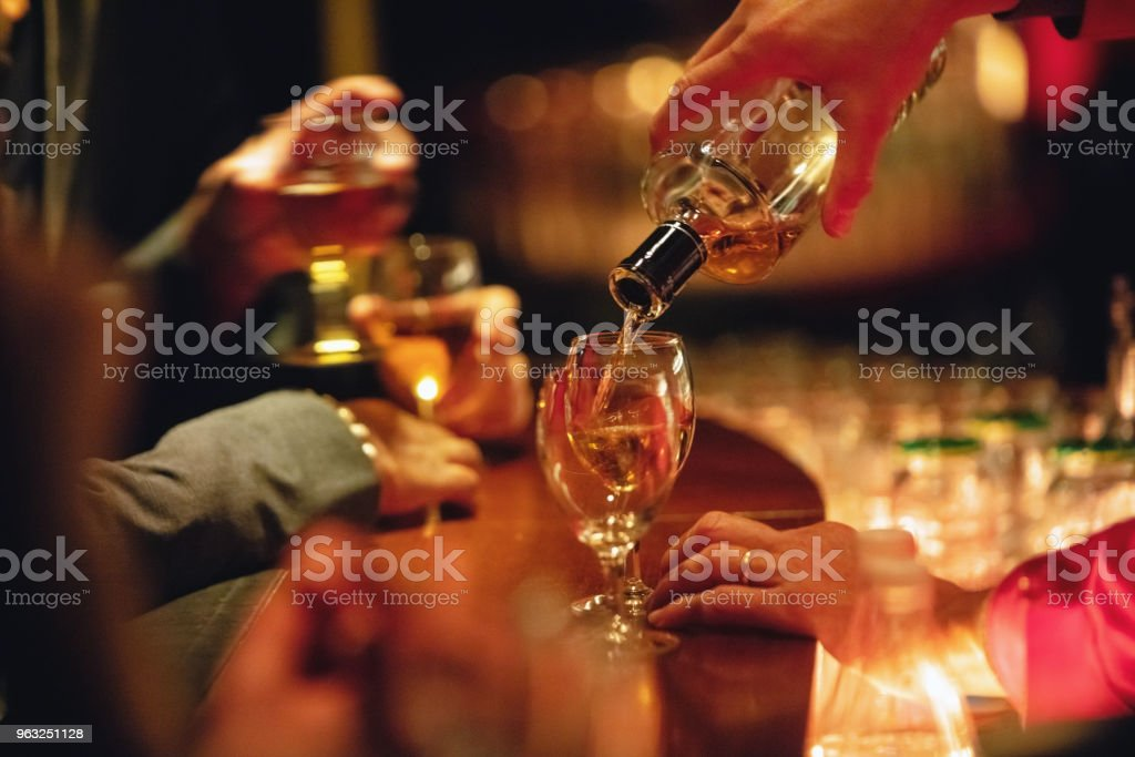 Bartender pouring alcoholic drinks stock photo