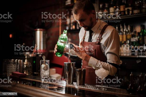 Bartender pouring an alcohol from the measuring cup into the steel picture id1027093074?b=1&k=6&m=1027093074&s=612x612&h=efgubpuau9gpc0aavhyzpoiv4of1cqsijeagskmdpi4=