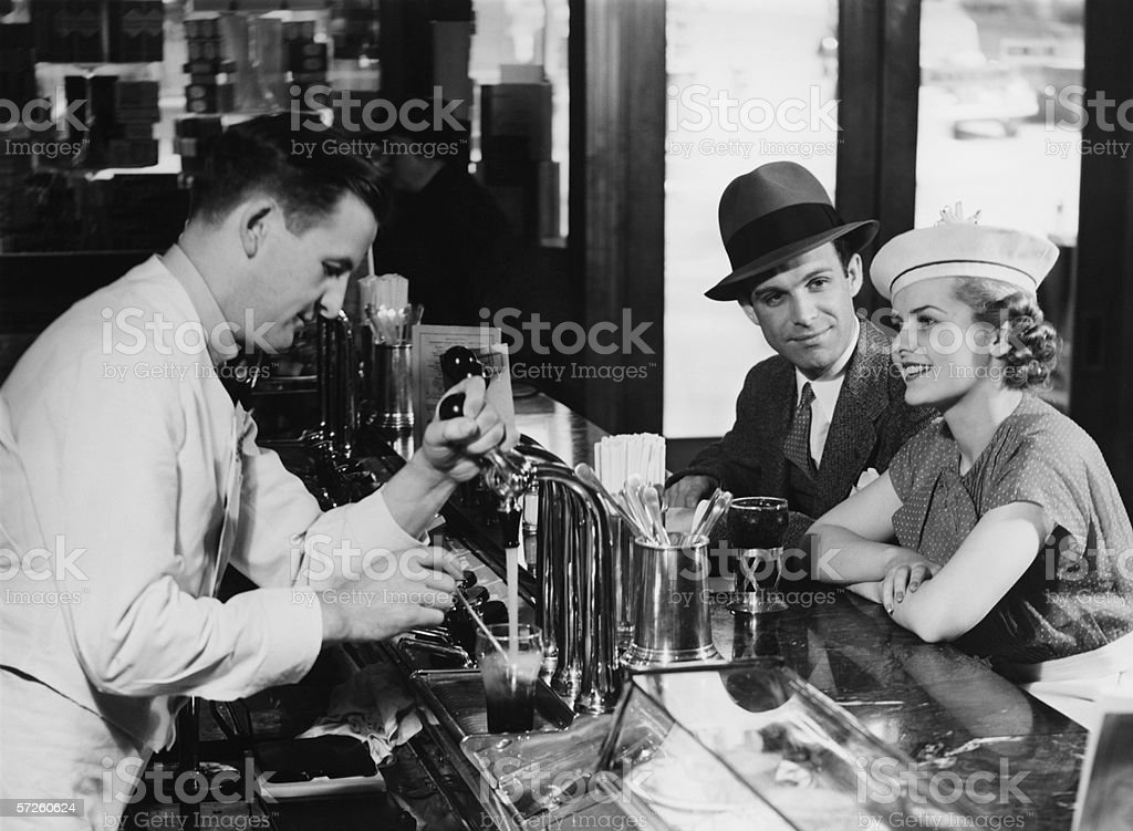 Bartender pouring beer for young couple in bar, (B&W) stock photo