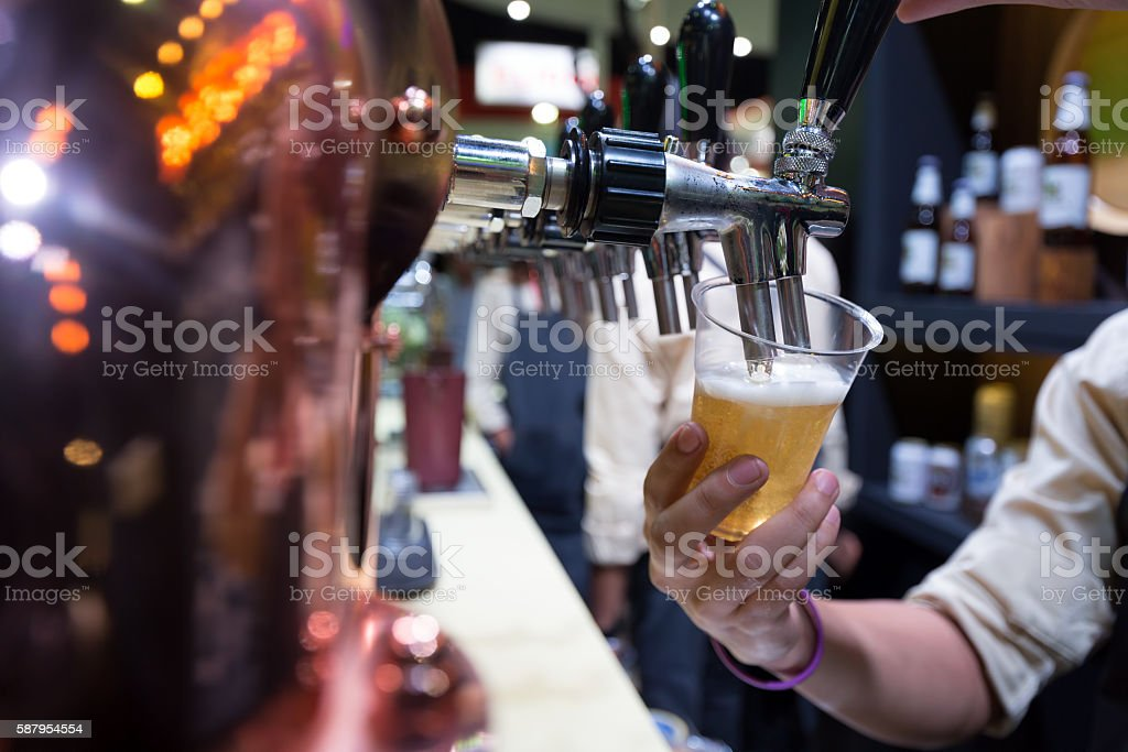 Bartender pouring beer stock photo