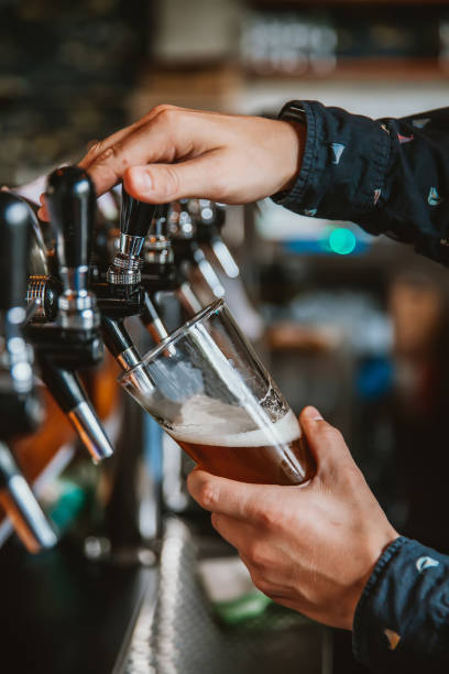 bartender pouring beer - beer pour stock photos and pictures
