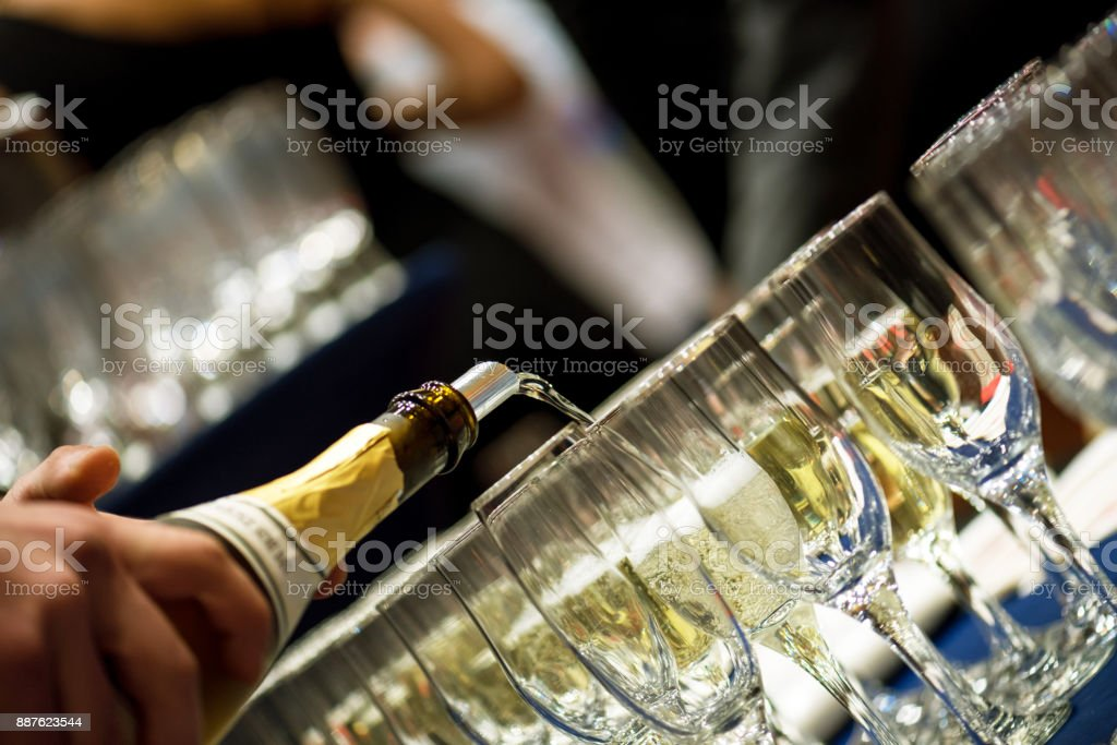 Bartender pouring champagne into glass. stock photo