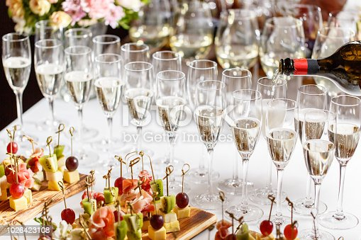 istock Bartender pouring champagne or wine into wine glasses on the table in restaurant. solemn wedding ceremony or happy new year banquet 1026423108
