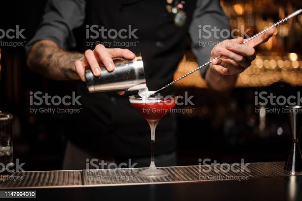 Bartender pouring cocktail using shaker and spoon picture id1147994010?b=1&k=6&m=1147994010&s=612x612&h=kzhwt7dh gjwpc6yrcyhzvlw5gsikvdcqrrgsdr3pm4=