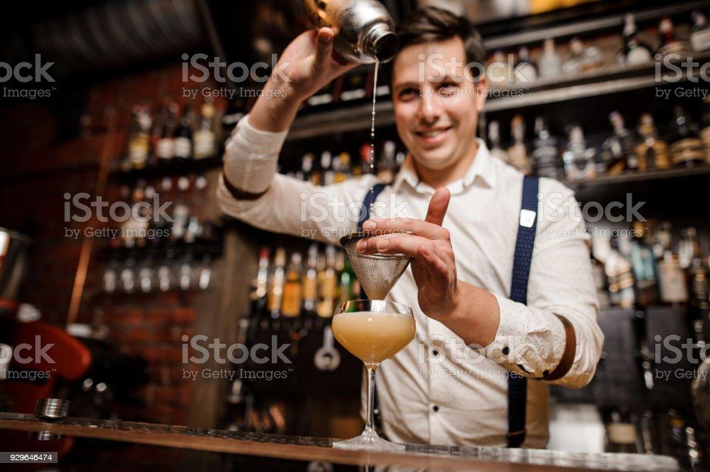 Barkeeper Cocktail in das Glas gießen und lächelnd – Foto
