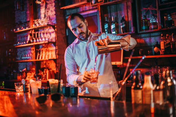 Bartender pouring drinks into shot glasses from a drink shaker in a pub Barkeeper pouring shots from a shaker at a bar. bartender stock pictures, royalty-free photos & images