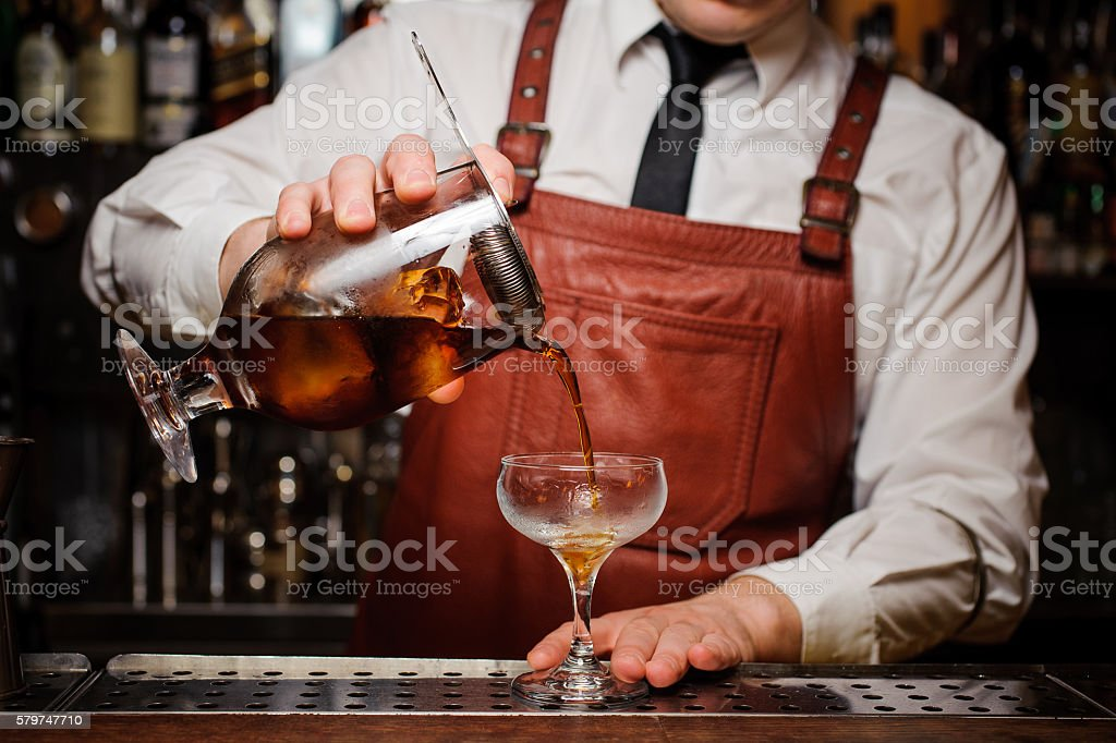 Bartender pouring fresh cocktail in fancy glass stock photo