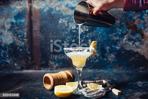 istock Bartender pouring fresh lime margarita in fancy glass at restaurant 533454946