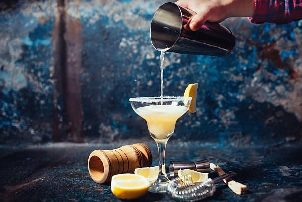 Bartender pouring fresh lime margarita in fancy glass at restaurant stock photo