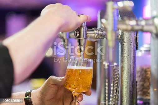 istock Bartender pouring lager beer in a glass. Shallow dof, selective focus. 1060126564