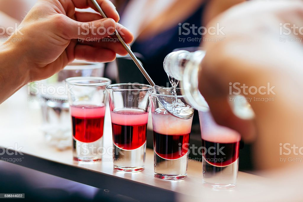 Bartender pouring shots cocktails stock photo