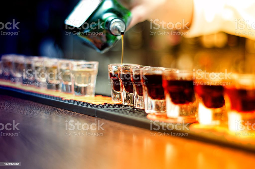 Bartender pouring strong alcoholic drink into glasses stock photo