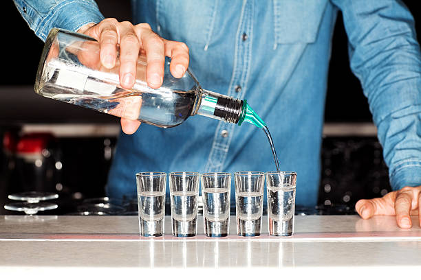 Bartender Pouring Vodka Into Shot Glasses At Bar Counter Midsection of male bartender pouring vodka into shot glasses at bar counter. Horizontal shot. vodka stock pictures, royalty-free photos & images