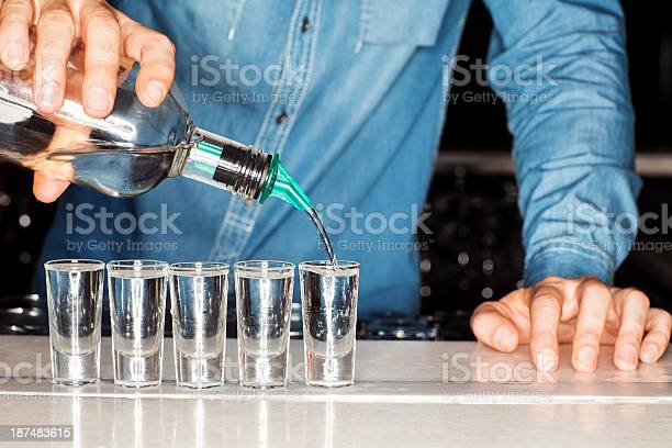 Bartender pouring vodka into shot glasses at counter picture id187483615?b=1&k=6&m=187483615&s=612x612&h=njqdvuwgzyhxjaxzvjoytdfa lrduyfafwsnmgzayjy=