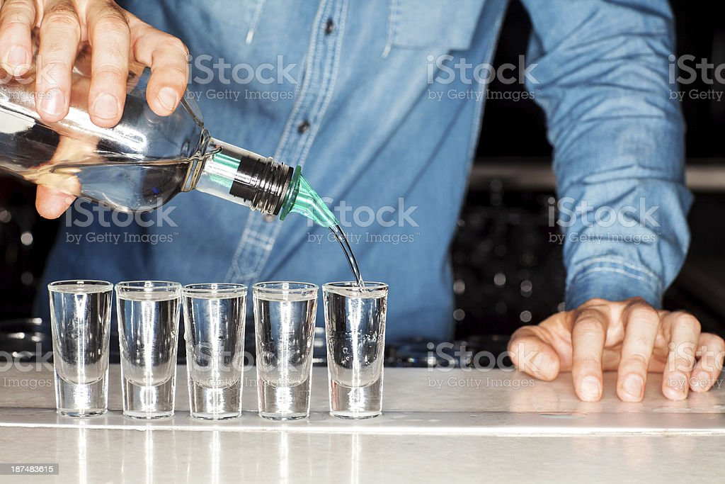 Bartender Pouring Vodka Into Shot Glasses At Counter stock photo