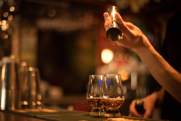 Bartender pouring whisky in a glass stock photo