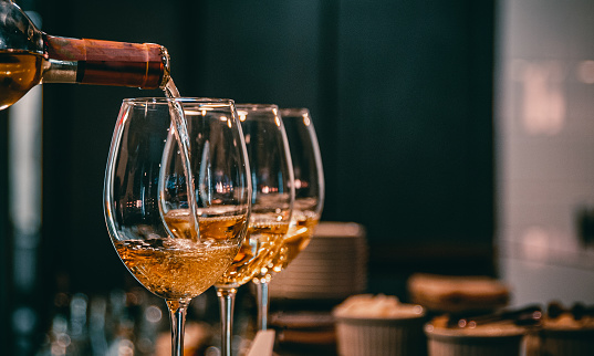 bartender pouring white wine into a glass in cafe or bar