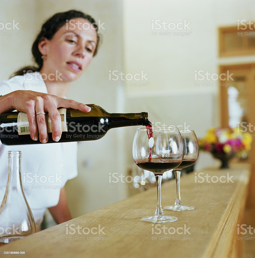 Bartender pouring wine into glass stock photo