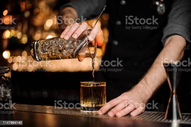 Bartender pours an alcohol cocktail adding whiskey picture id1147994140?b=1&k=6&m=1147994140&s=612x612&h=ok31cjjlc  v hlsfo3pqxwihb1gms tftrhgwch5b4=