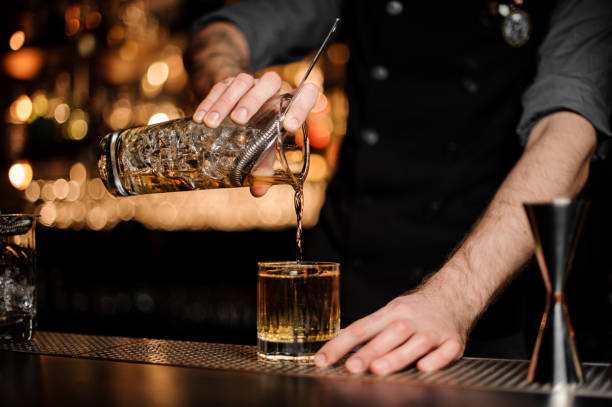 bartender pours an alcohol cocktail adding whiskey - bar foto e immagini stock