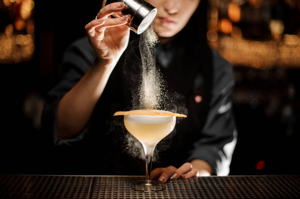 Bartender pours an alcohol cocktail in glass Female bartender pours an alcohol light brown cocktail with sour mix in glass bartender stock pictures, royalty-free photos & images