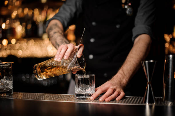 Bartender pours cocktail adding whiskey in glass Male bartender with tattoos pours alcohol cocktail adding cold whiskey in glass bartender stock pictures, royalty-free photos & images