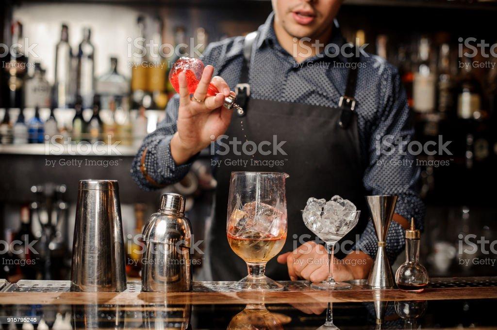 Barkeeper gießt Sirup in cocktail-Glas mit Eis – Foto