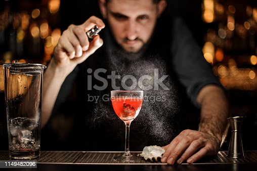 Male bartender with beard in gray shirt pours the alcohol cocktail with oyster using steel sprayer with big glass with sieve