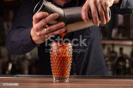 istock bartender pours tomato red juice from the shaker, making a cocktail, drink 1070464360