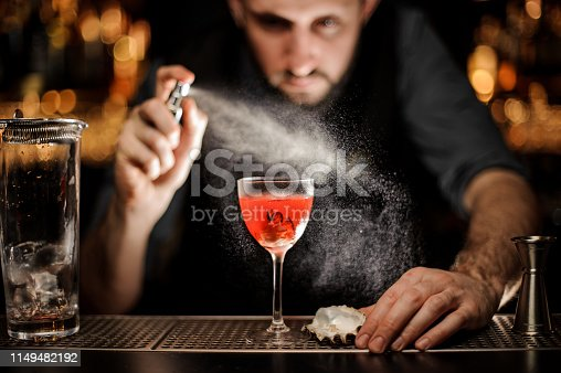 istock Bartender prepares alcohol cocktail with a sprayer 1149482192