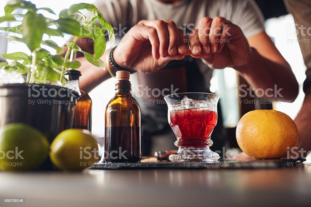 Bartender preparing cocktail with grapefruit stock photo