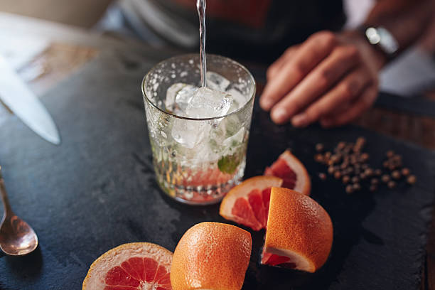 bartender preparing exotic cocktail. - grapefruit cocktail stock photos and pictures