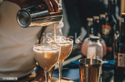 Close up male bartender hands making Baileys cocktail with ice and pouring to glass from bar shaker
