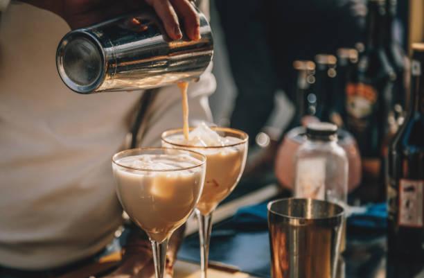Bartender preparing  Irish Cream Liqueur cocktail with shaker stock photo