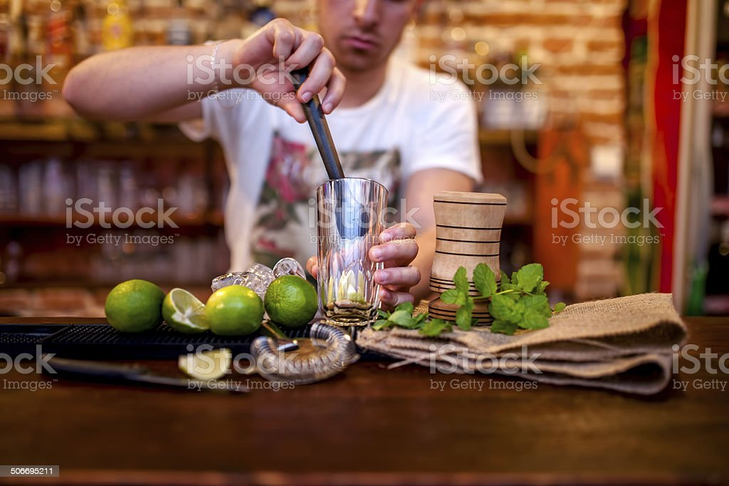 bartender preparing mojito cocktail drink, with limes, ice and sugar stock photo