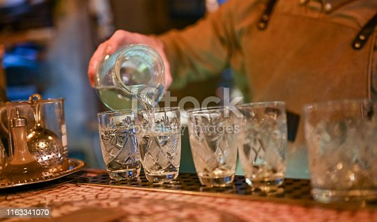 Close-up of unrecognizable bartender pouring vodka
