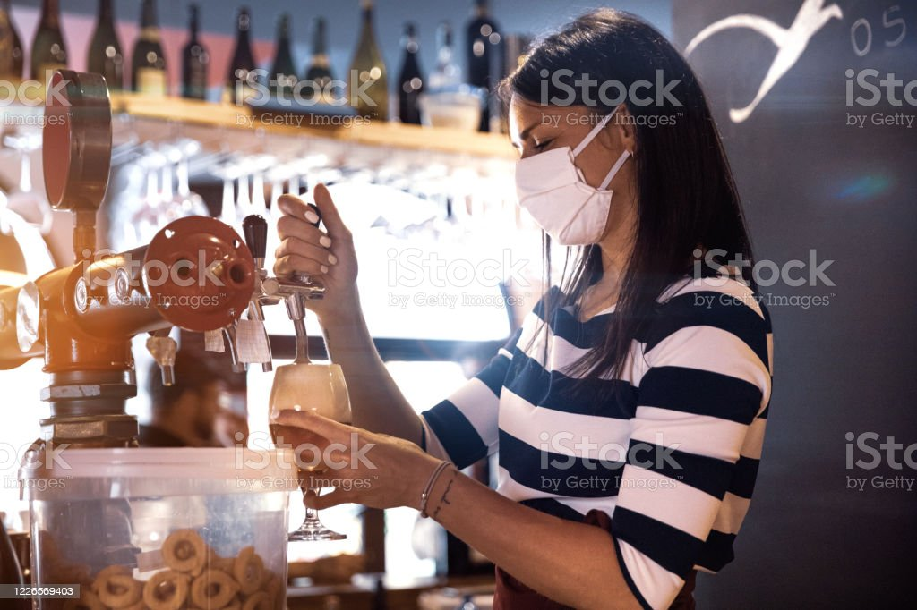 Bartender serves a fresh beer in a pub Bartender serves a fresh beer in a pub in the pandemic days, wearing protective face mask. 30-34 Years Stock Photo