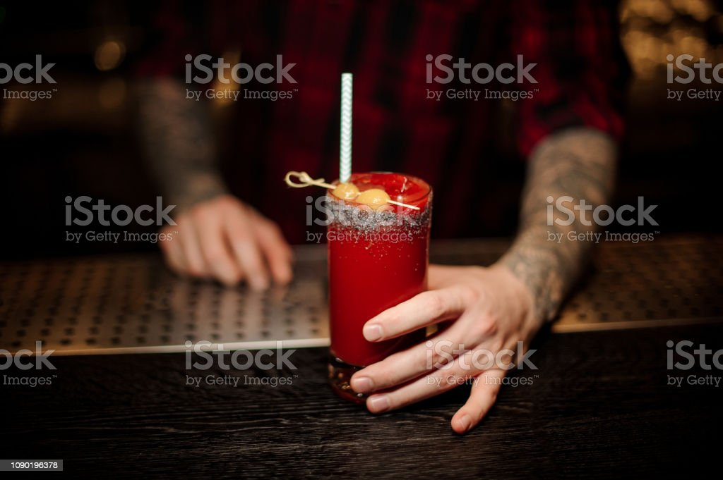 Bartender serving a Bloody Mary cocktail in the decorative glass with olives and tubule stock photo