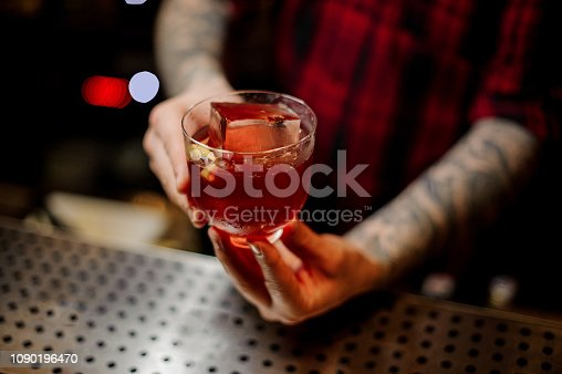 Bartender serving a glass of a Vieux Carre cocktail with big ice cube and orange zest on the steel bar counter on the blurred background