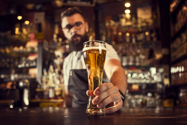 Bartender serving beer Bartender serving beer in a bar bartender stock pictures, royalty-free photos & images
