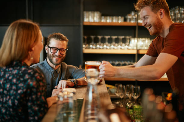 Bartender serving beer to customers. Pub interior. stock photo
