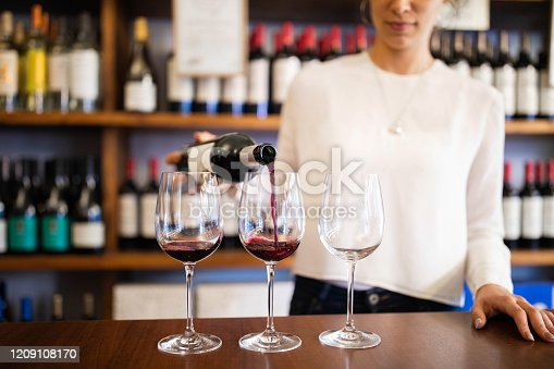 Close-up of a female waiter pouring wine from bottle into three glasses on counter. Sommelier serving red wine in a winery store.