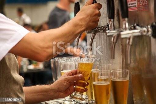 1144550840 istock photo Bartender serving tap beer on a unfocused party background 1158048241