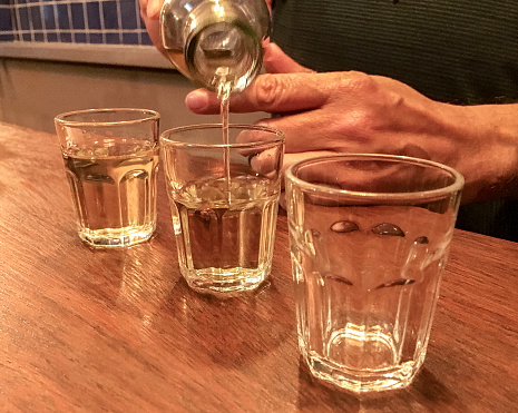 Bartender serving three doses of cachaça