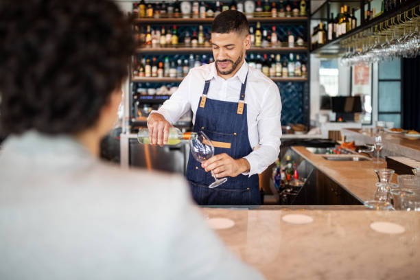 Bartender serving wine to a woman stock photo