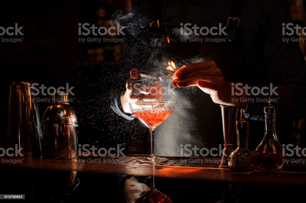 Bartender setting fire to sweet cocktail in bocal stock photo
