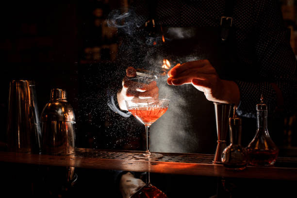 bartender setting fire to sweet cocktail in bocal - bartender стоковые фото и изображения