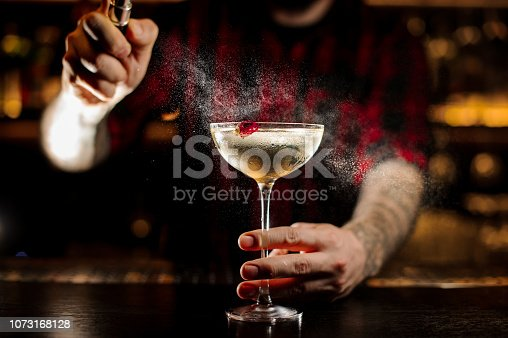 Bartender spraying on a glass of a delicious Twinkle cocktail with one berry on the bar counter on the blurred dark and yellow light background
